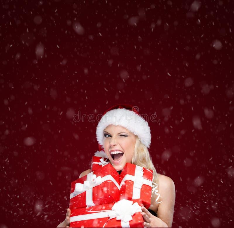 圣诞节盖帽的俏丽的妇女拿着一套礼物 免版税库存照片