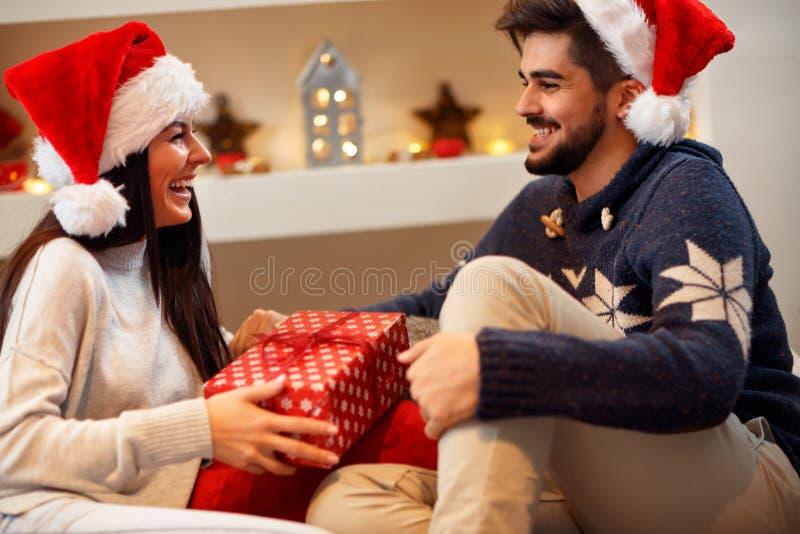 圣诞节礼品 在圣诞老人` s帽子的愉快的夫妇有圣诞节礼物的 图库摄影
