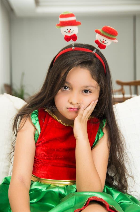 圣诞节礼服的乏味小女孩 免版税库存照片