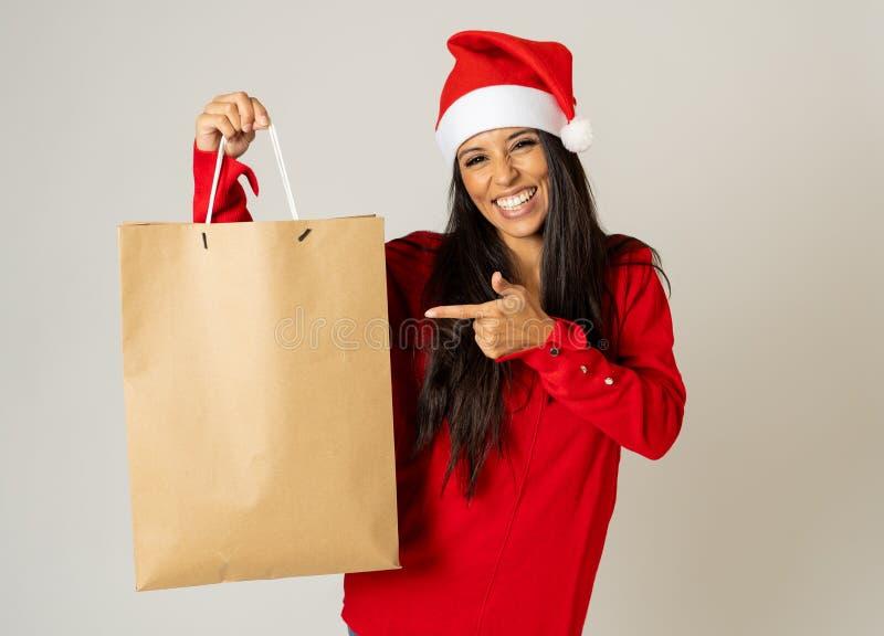 圣诞节礼物与购物袋和看起来圣诞老人的帽子的妇女购物激发和愉快 免版税库存图片