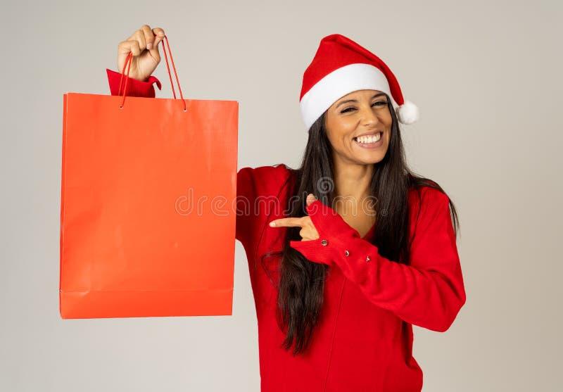 圣诞节礼物与购物袋和看起来圣诞老人的帽子的妇女购物激发和愉快 库存照片