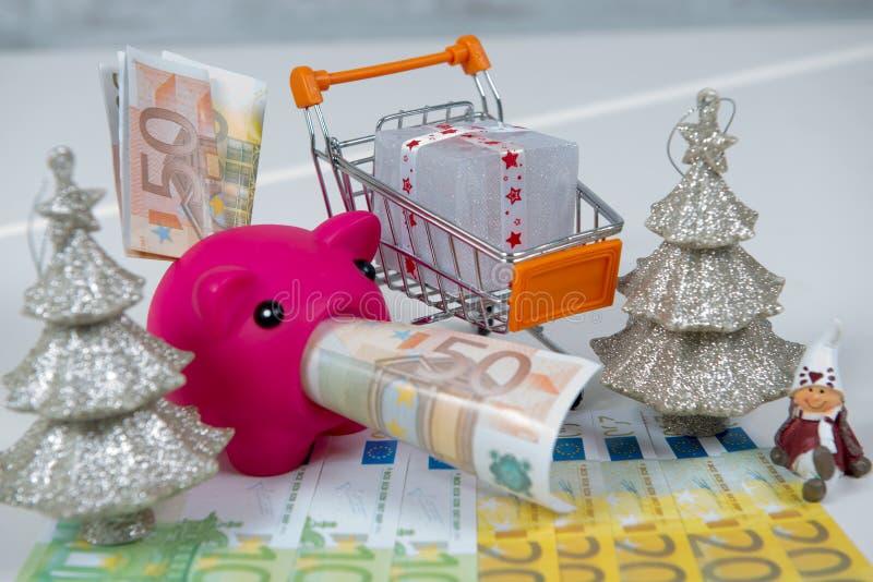 圣诞节礼物在购物车、金钱和存钱罐中 免版税图库摄影