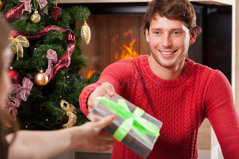 给圣诞节礼物的微笑的人 免版税库存照片
