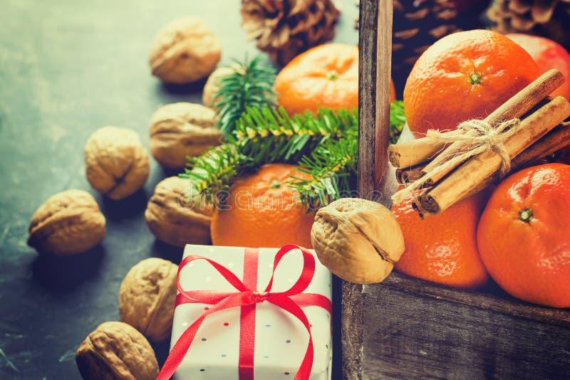 圣诞节礼物盒用在木箱子的红色丝绸丝带蜜桔肉桂条杉树分支杉木锥体核桃 图库摄影