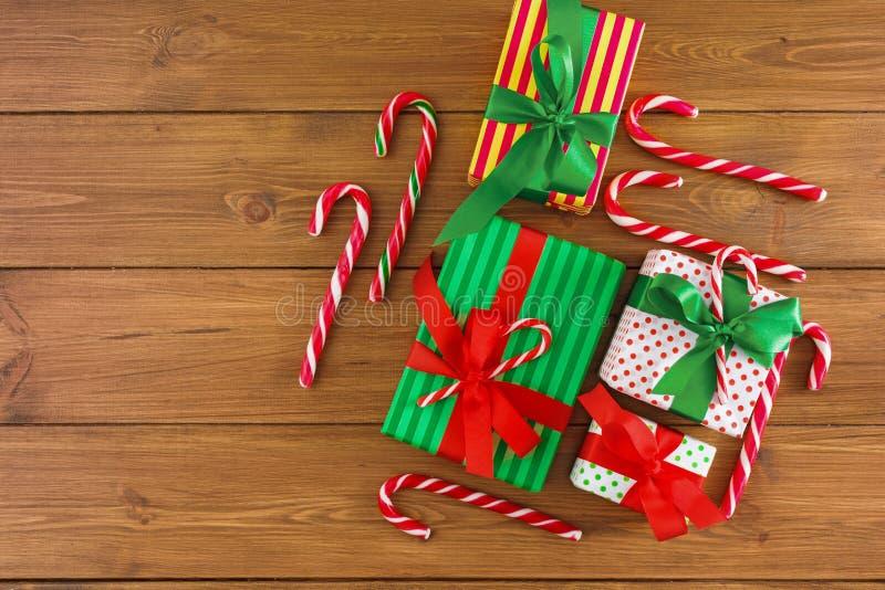 圣诞节礼物盒,在土气背景的糖果 用红色,绿色丝带装饰的礼物鞠躬 顶视图 库存照片