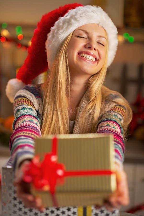 给圣诞节礼物箱子的圣诞老人帽子的女孩 库存照片
