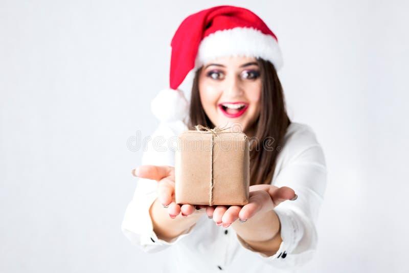 圣诞节礼物weihnachtspakete 美丽的妇女加上大小在圣诞老人帽子 免版税库存图片