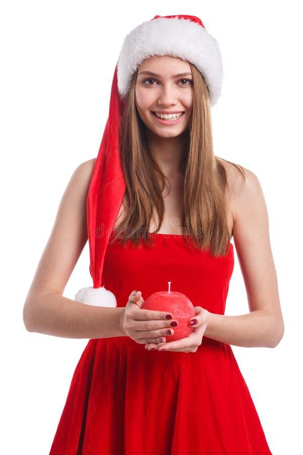 圣诞节穿戴和举在红色和圆形的圣诞老人帽子的微笑的女孩一个蜡烛 背景查出的白色 库存图片