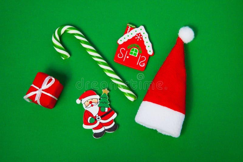 圣诞节糖果、圣诞老人帽子和礼物盒在绿色背景,顶视图 库存图片