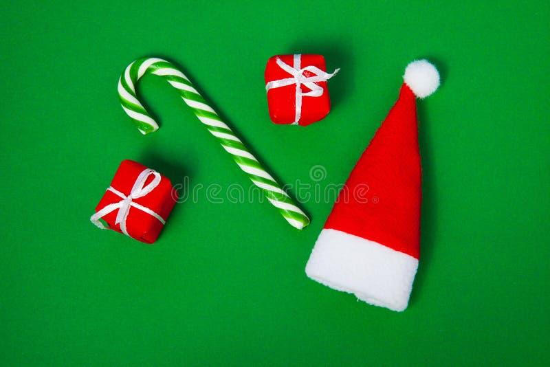圣诞节糖果、圣诞老人帽子和礼物盒在绿色背景,顶视图 免版税库存照片