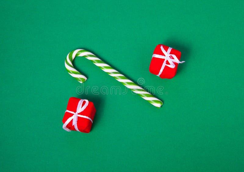 圣诞节糖果和礼物盒在绿色背景,顶视图 库存图片