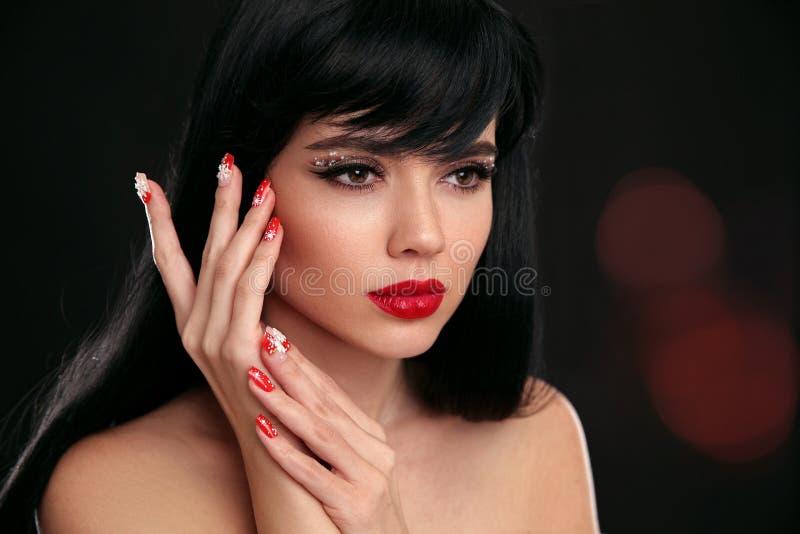 圣诞节红色嘴唇构成和被修剪的钉子 美好的brunett 免版税库存照片