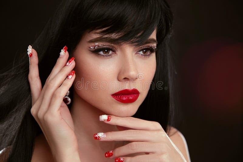 圣诞节红色嘴唇构成和被修剪的钉子 美好的brunett 库存照片