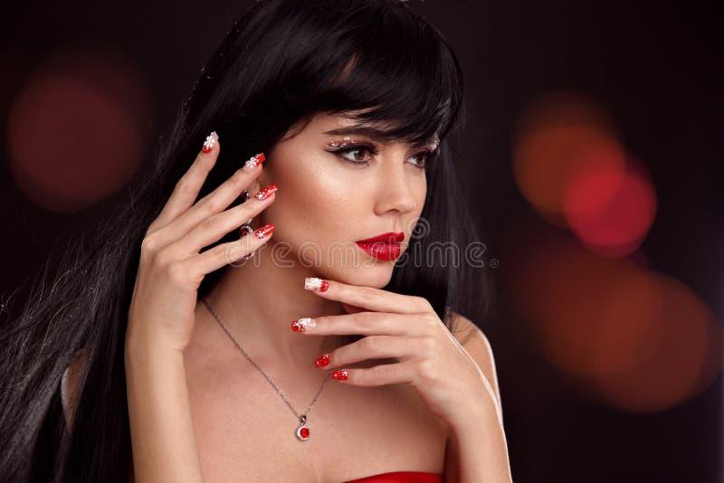 圣诞节红色嘴唇构成和被修剪的钉子 美好的brunett 免版税库存图片