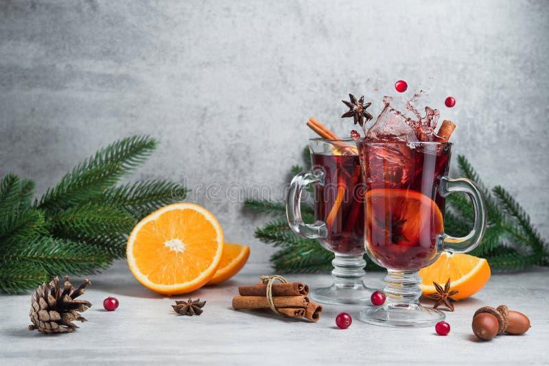 圣诞节红色在玻璃的加香料的热葡萄酒飞溅 免版税库存图片