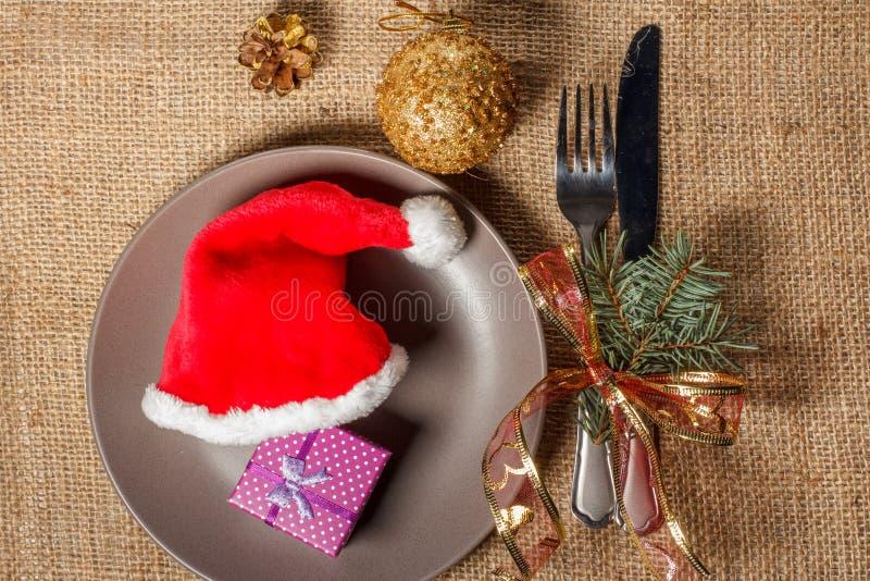 圣诞节红色帽子和礼物在礼物盒在板材、叉子和kni 库存照片
