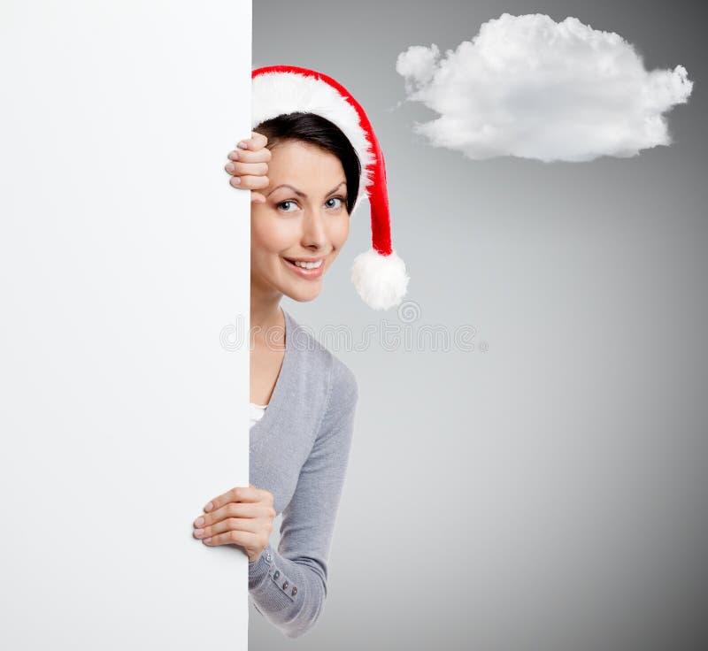 圣诞节红色盖帽的俏丽的兴高采烈的妇女 库存图片