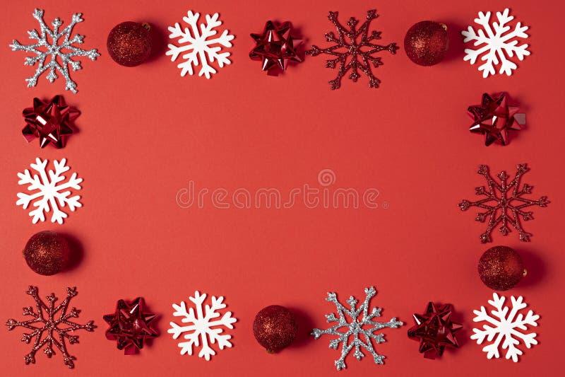 圣诞节红色背景顶视图 假日新年球,与框架的圣诞节装饰雪花的设计 免版税图库摄影
