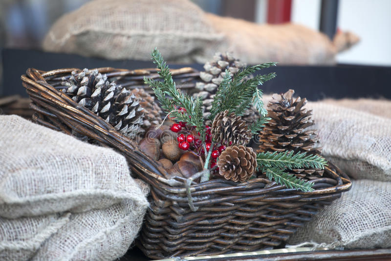 圣诞节红色装饰品,多雪的装饰的杉木锥体桌焦点 与安排的圣诞节背景在柳条筐 免版税库存照片