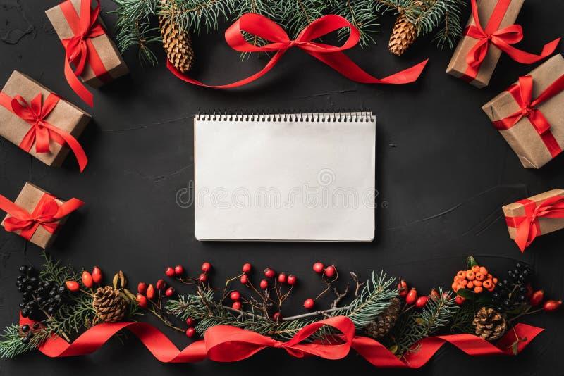 圣诞节结构的冷杉分支、杉木锥体、莓果、礼物和红色松驰,在黑石背景 免版税库存照片