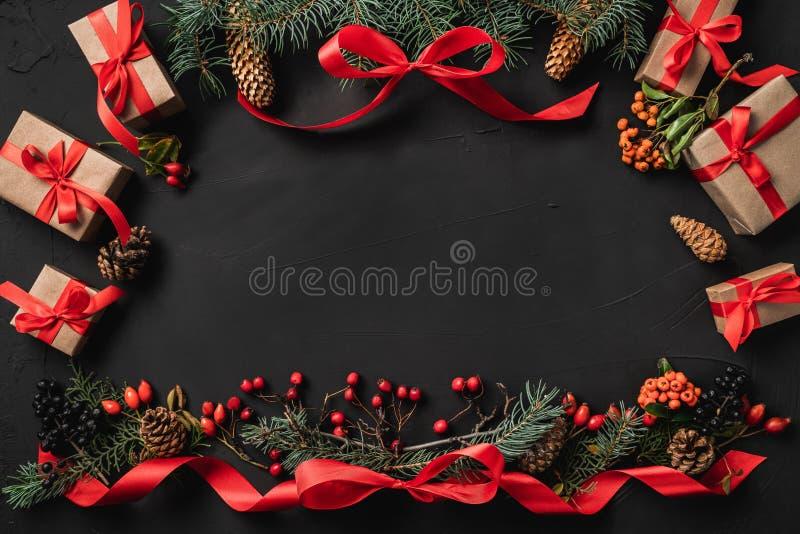圣诞节结构的冷杉分支、杉木锥体、莓果、礼物和红色松驰,在黑石背景 图库摄影