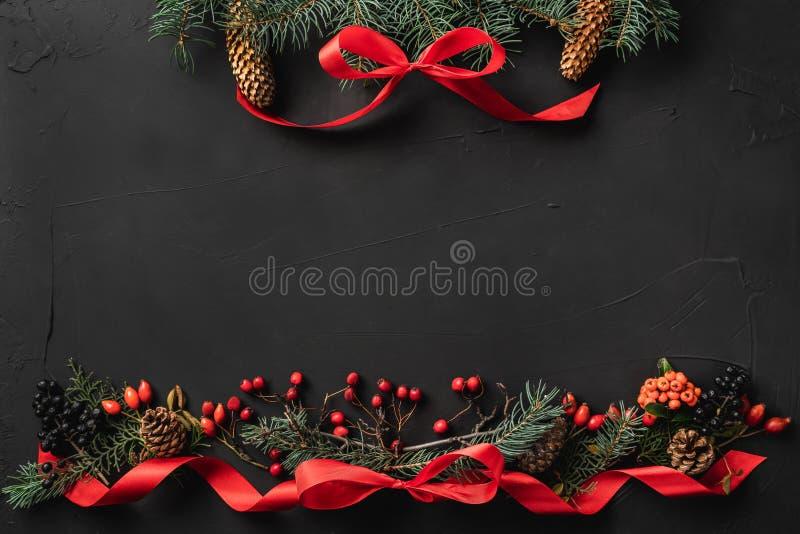 圣诞节结构的冷杉分支、杉木锥体、莓果、礼物和红色松驰,在黑石背景 免版税库存图片