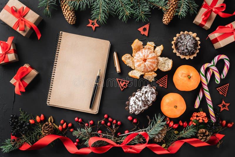 圣诞节结构的冷杉分支、杉木锥体、莓果、礼物和红色松驰,在黑石背景 库存图片