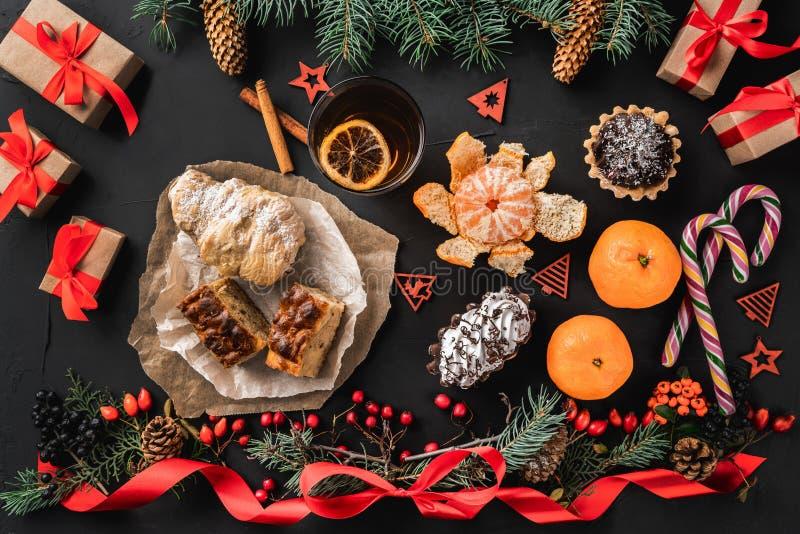 圣诞节结构的冷杉分支、杉木锥体、莓果、礼物和红色松驰,在黑石背景 库存照片