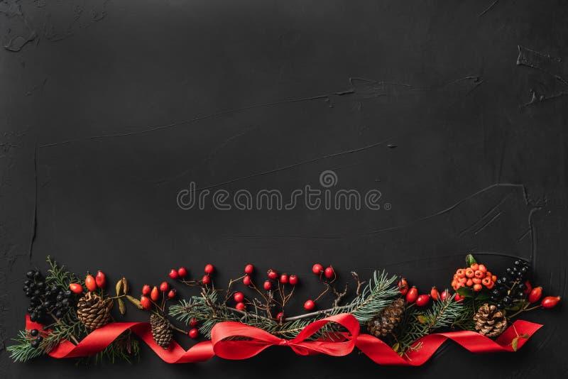 圣诞节结构的冷杉分支、杉木锥体、莓果和红色松驰,在黑石背景 免版税库存照片