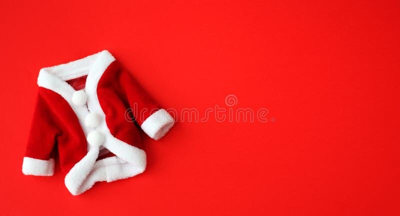 圣诞节背景圣诞老人项目圣尼古拉斯微型外套衣服服装白色袖口平展放置被隔绝的五颜六色的红色背景 库存照片