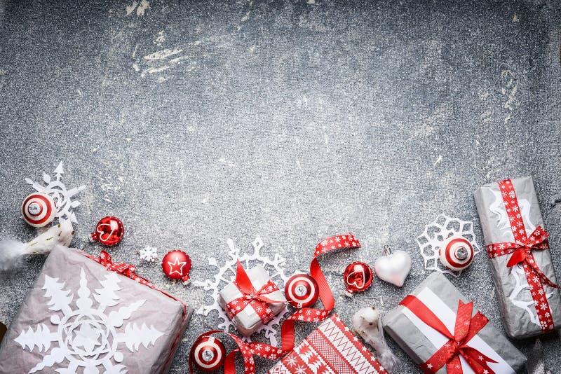 圣诞节背景欢乐礼物盒和礼物、纸雪花、红色丝带和装饰 免版税库存照片