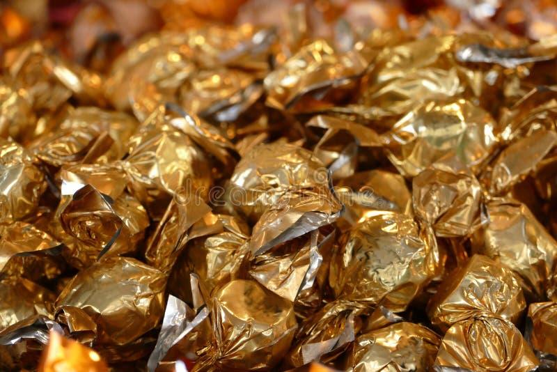 圣诞节背景,在金黄金属箔包裹的糖果 免版税库存图片