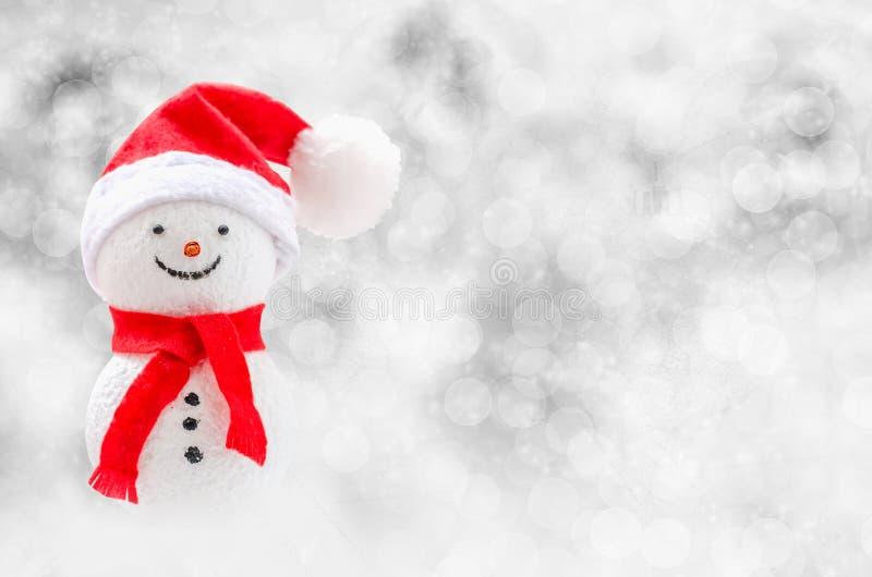 圣诞节背景-与红色围巾和红色帽子o的逗人喜爱的雪人 免版税库存照片