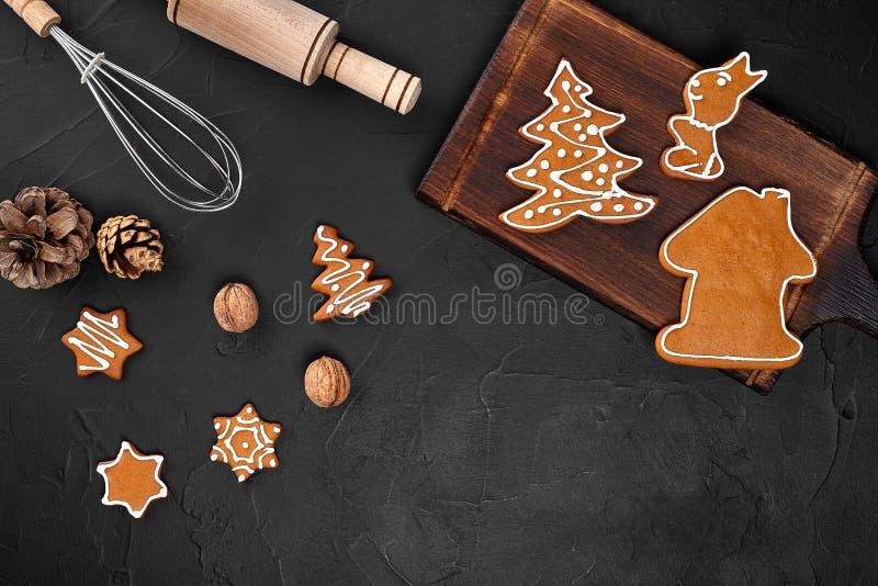 圣诞节自创姜饼曲奇饼、香料和切板在黑暗的背景与拷贝空间文本顶视图的 库存照片
