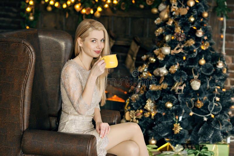 圣诞节舒适内部的少妇  女孩坐与一个黄色杯子在许多礼物中的一棵圣诞树下 Prepa 图库摄影