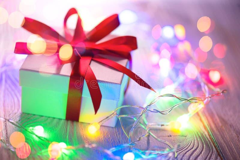 圣诞节节假日背景 有红色丝绸丝带的被包裹的礼物盒和在木背景的五颜六色的光诗歌选 库存照片