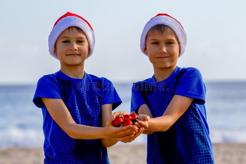 圣诞节节假日 在拿着圣诞节装饰的红色圣诞老人帽子的孩子在晴朗的海滩 免版税库存图片