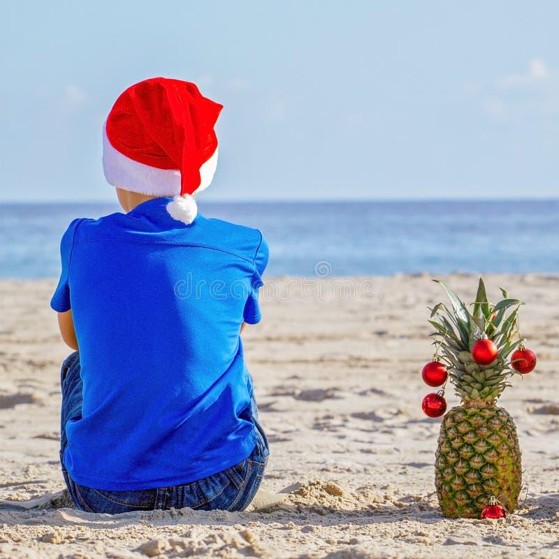 圣诞节节假日 红色作为在一个晴朗的沙滩的一棵圣诞树装饰的圣诞老人帽子和菠萝的男孩由海 免版税库存照片