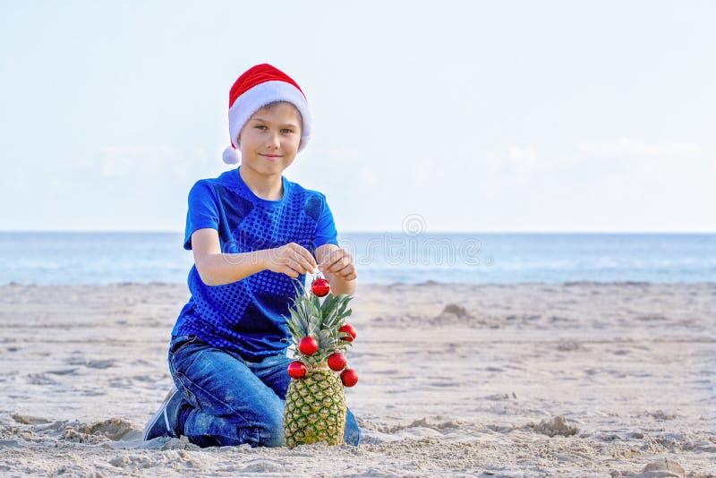 圣诞节节假日 红色圣诞老人帽子的男孩装饰菠萝的作为在一个晴朗的沙滩的一棵圣诞树由海 免版税库存图片