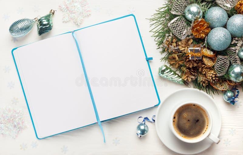 圣诞节花圈、咖啡和在白色背景的空白的开放笔记薄 免版税库存图片