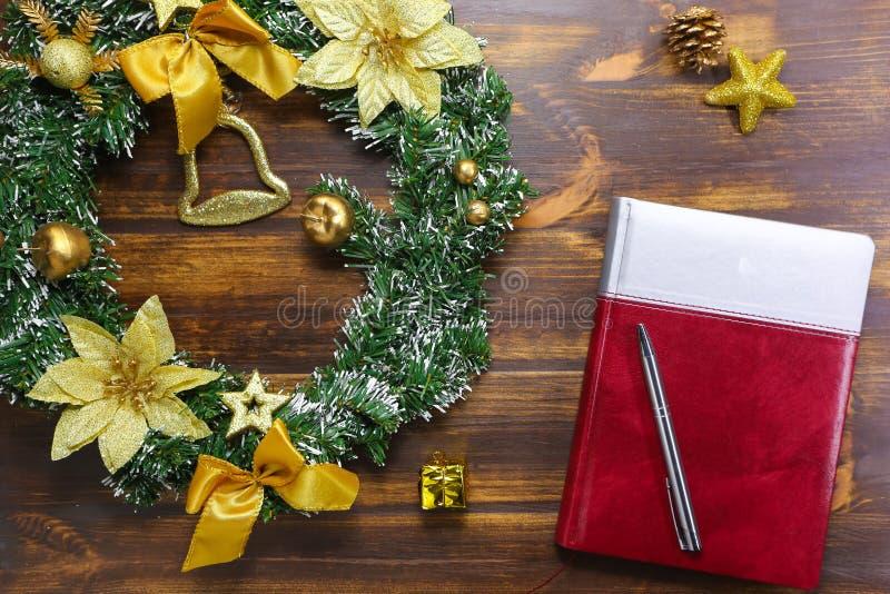 圣诞节花圈和笔记本在木桌投入了 节假日 免版税图库摄影