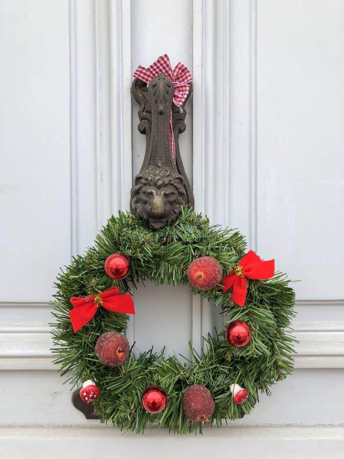 圣诞节花圈用在一个白色门的红色苹果 免版税库存图片
