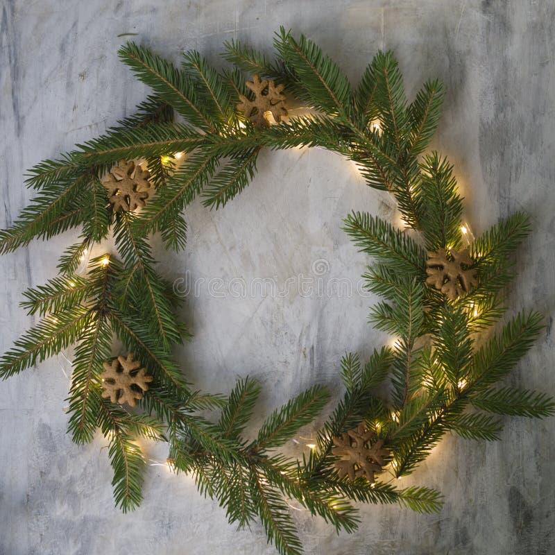 圣诞节花圈由冷杉分支、曲奇饼和发光的光做成在灰色背景 背景新年度 圣诞节 免版税图库摄影
