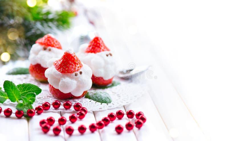 圣诞节草莓圣诞老人 用打好的奶油充塞的滑稽的点心 免版税图库摄影