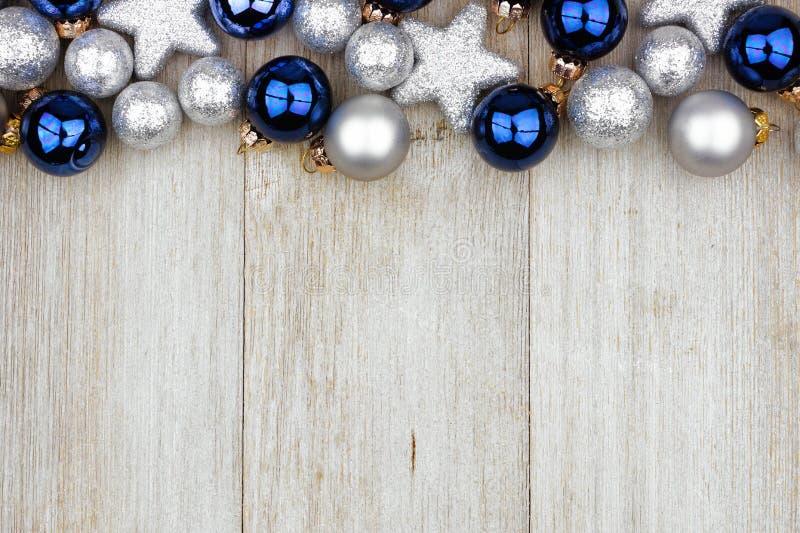 圣诞节蓝色和银色装饰品上面边界在灰色木头的 免版税库存图片