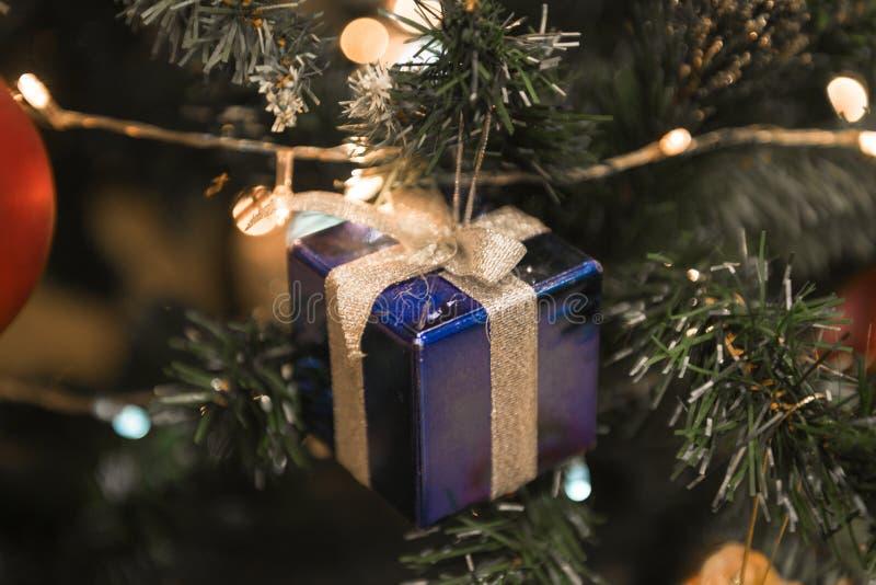 圣诞节蓝色当前垂悬在一美好的Chrismas树surr 库存图片