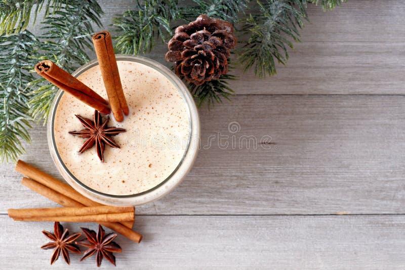 圣诞节蛋黄乳,与树枝壁角边界的顶视图在灰色木头的 免版税库存图片
