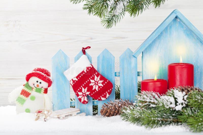 圣诞节蜡烛、雪人玩具和杉树 免版税库存照片