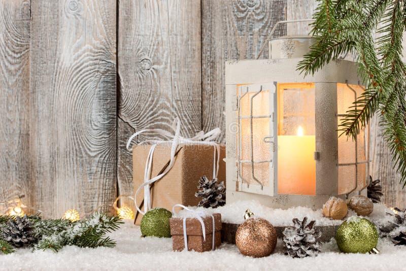 圣诞节蜡烛灯笼、礼物盒和装饰在雪 库存图片