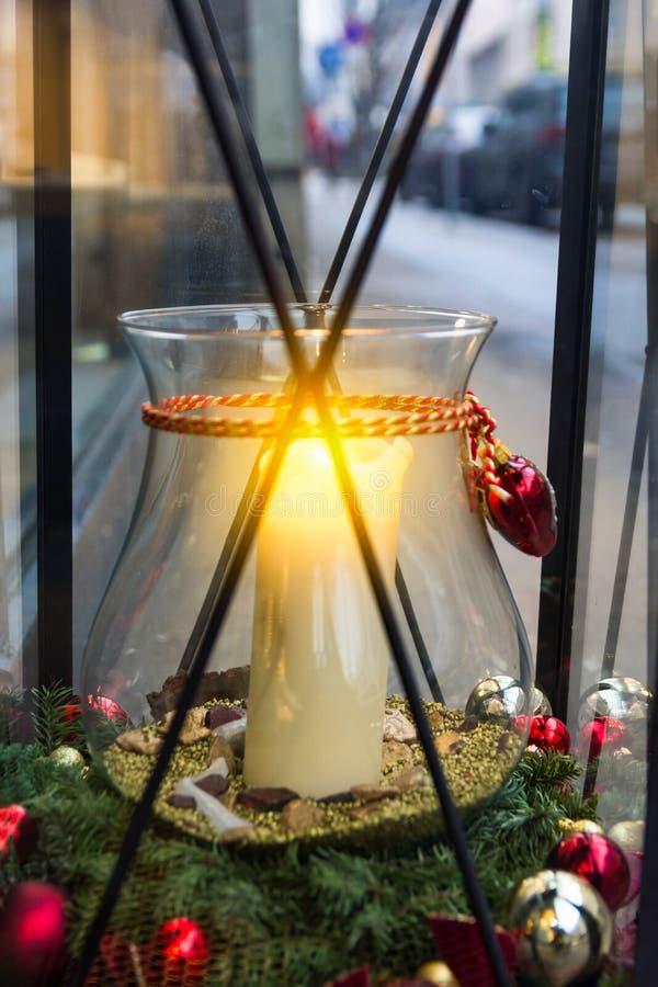 圣诞节街道装饰 在瓶子烛台的大白色灼烧的蜡烛在大葡萄酒灯笼里面用新鲜的冷杉球装饰了 免版税库存图片